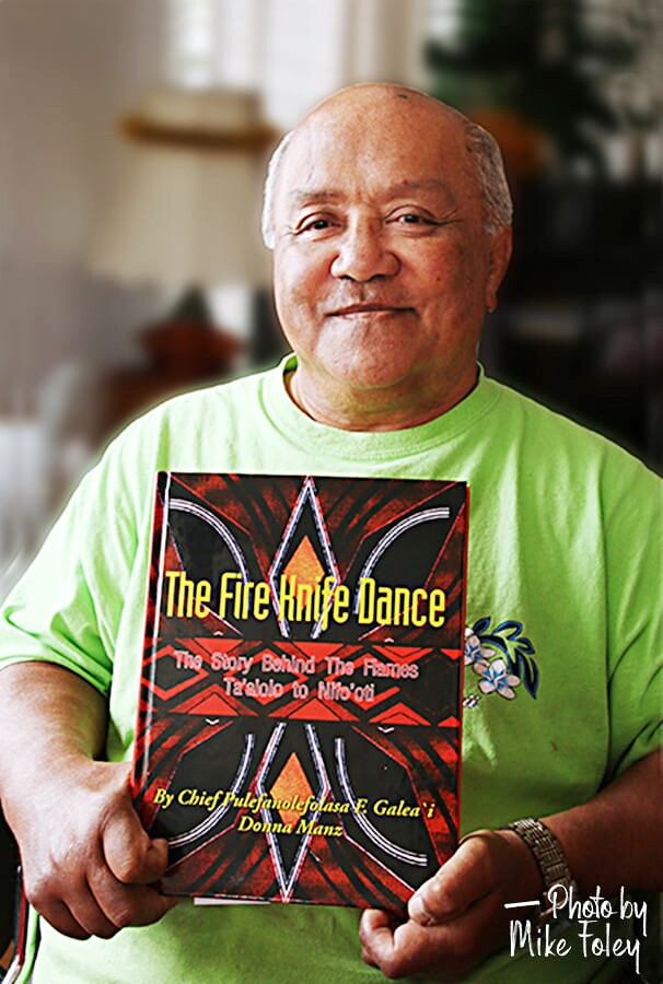 Pulefano Galea'i in a green T-shirt holding his book he wrote about fire knife dancing.