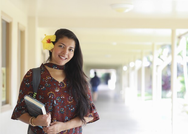 Image of a female student standing in a hallway smiling