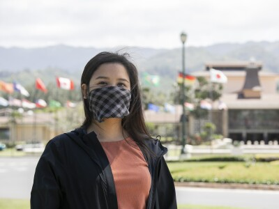 BYUH female student standing in front of the Flag Circle at BYU–Hawaii, wearing a mask.