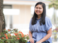 A smiling female BYU–Hawaii student in a blue dress sitting beside a bed of red flowers.