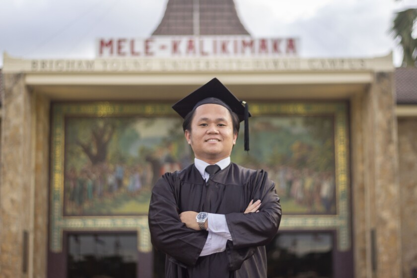 "Takin smiles and crosses his arms in a black graduation cap and gown with the BYUH campus mural and sign saying ""Mele Kalikimaka"" is in the background."