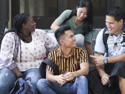 Four students sitting on the stairs while chatting casually.
