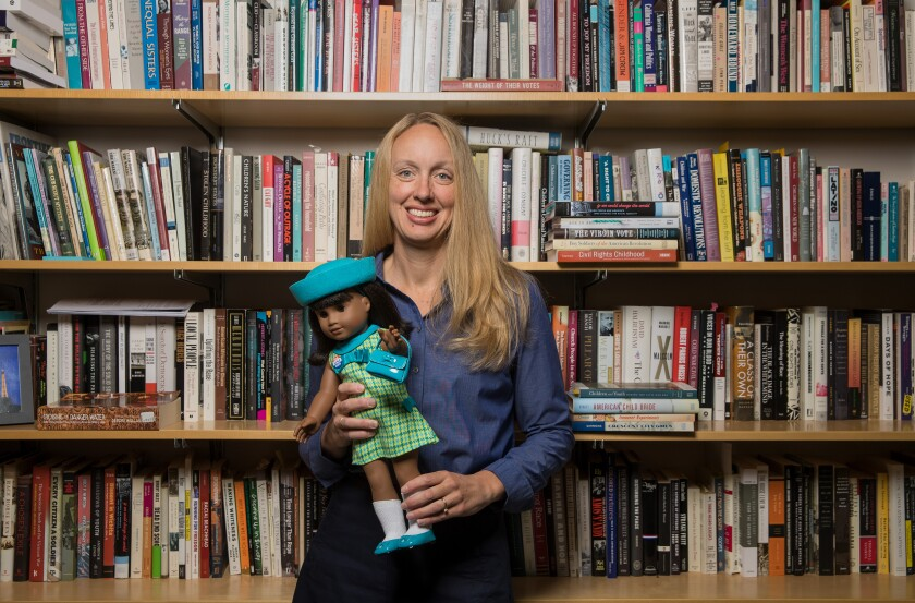 Rebecca de Schweinitz with American Girl Doll in front of bookshelf