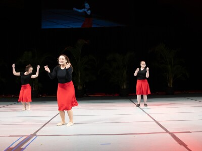 Six women wearing black shirts and red skirts hold their arms up while dancing on a white stage with a black background.