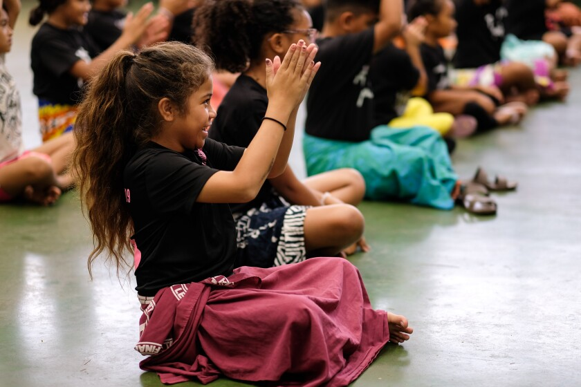 Girl in black shirt and maroon lavalava sits cross-legged on the floor clapping hands with other children lined up beside her.