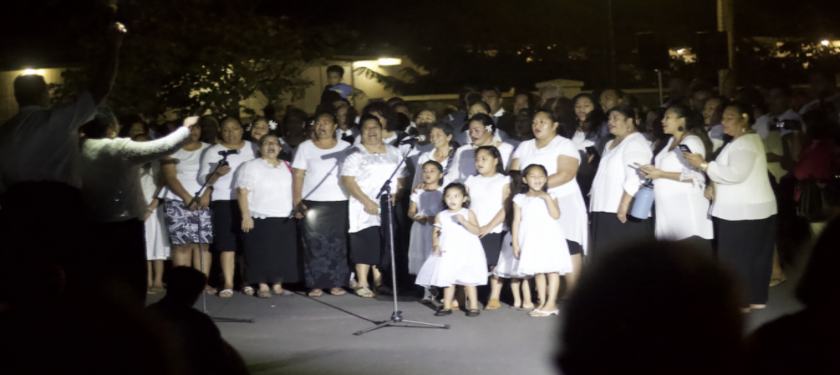 Members of the community dressed in Sunday clothes sing songs