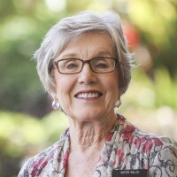 A portrait of Sister Jeannie Welch smiling at the camera with blurred green plants in the background.