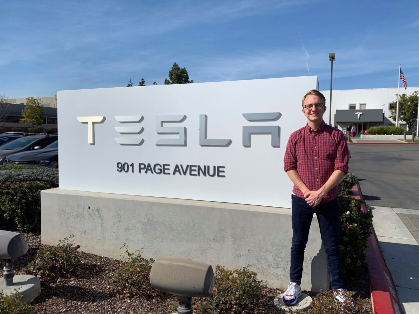 Tyler Lutz stands in front of one of Tesla's factories on 901 Page Avenue in Fremont, California
