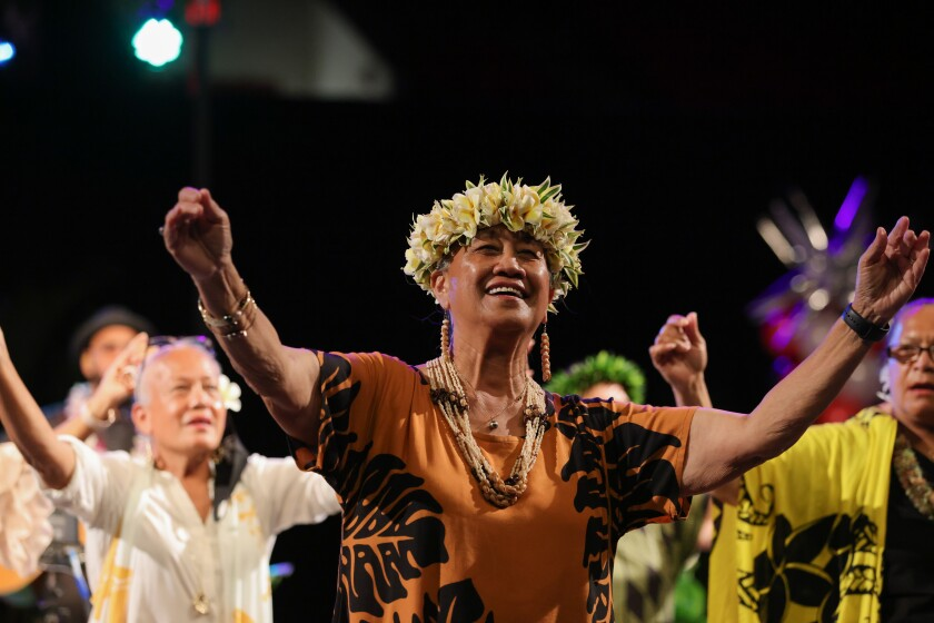 Kekela Miller is doing the hula wearing an orange dress with leaves, beaded jewelry and a flower haku on her head with other women behind her doing it too.
