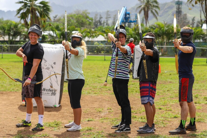 Five students in the archery event hold up their bows with foam-tipped arrows