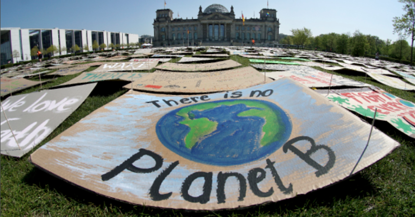 """Photo of the lawn outside of a parliament building in Berlin that has signs laid out on it with the front sign saying """"there is no planet B."""""""
