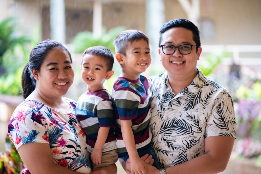 Dela Peña smiles while wearing a white and green-leafed shirt next to his wife, wearing a white with a blue, pink and purple floral pattern and both of them holding their two sons wearing striped shirts with greenery in the background.