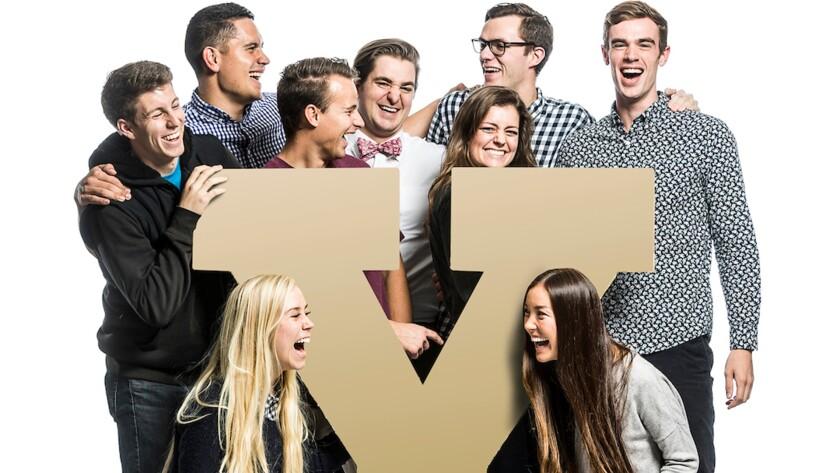 BYU students posing around the BYU logo