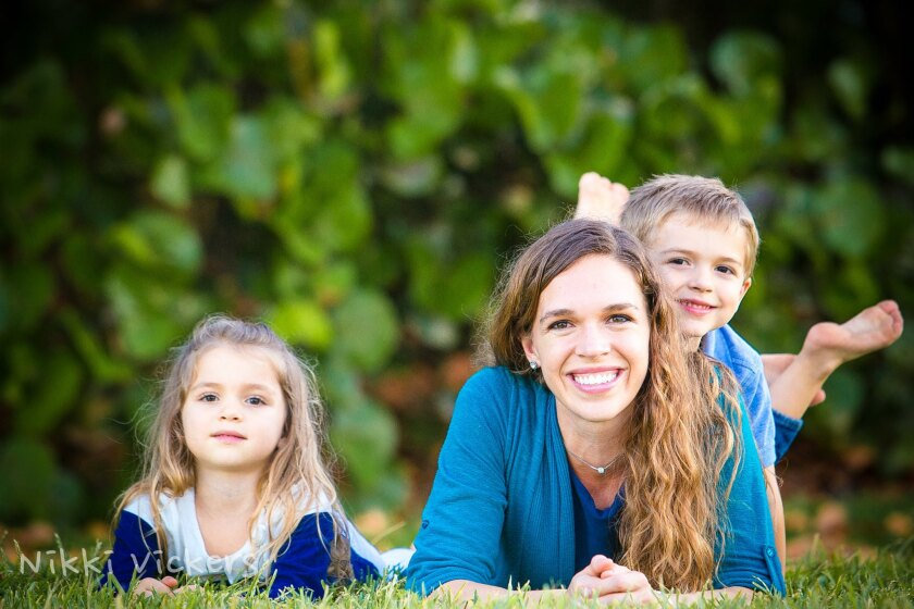 Shenley Puterbaugh lays on the grass smiling with her son on her back and her daughter on the left of her, all wearing blue