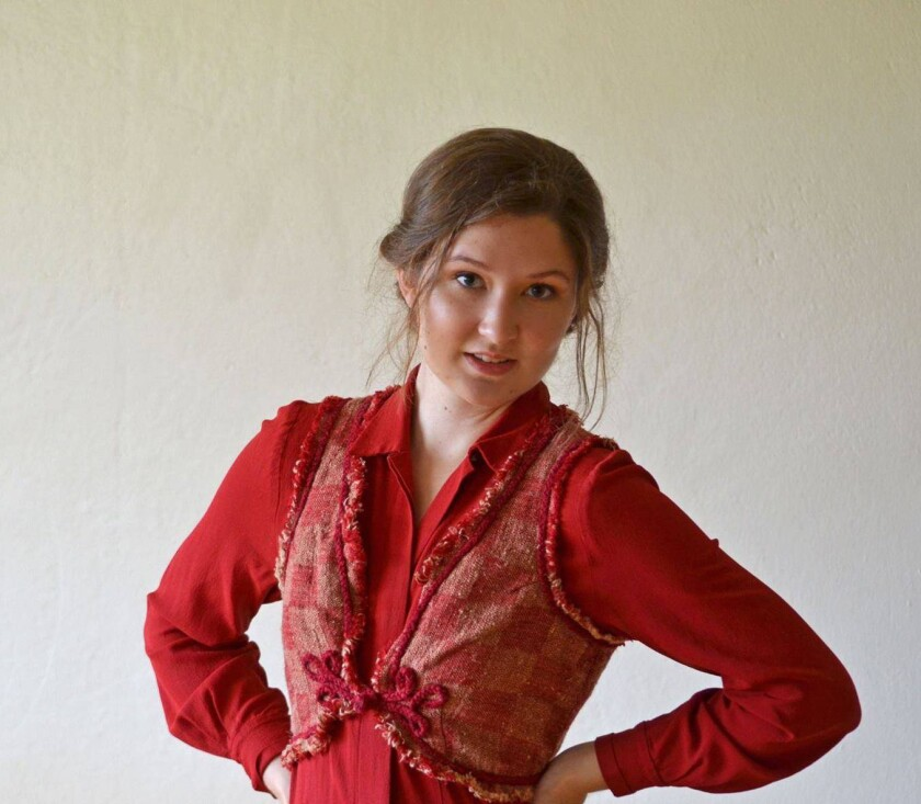 Kiaran Loefke wears a red long-sleeved blouse with her hair tied up behind her with a white-walled background.