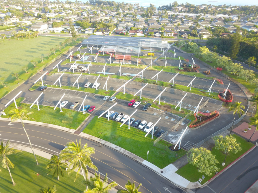Aerial view of Admin Parking. Naniloa Loop is at the top and Academic Oval is at the bottom of the parking. One-third of the parking near the Naniloa Loop has solar panels. The rest of the area has columns for solar panels.