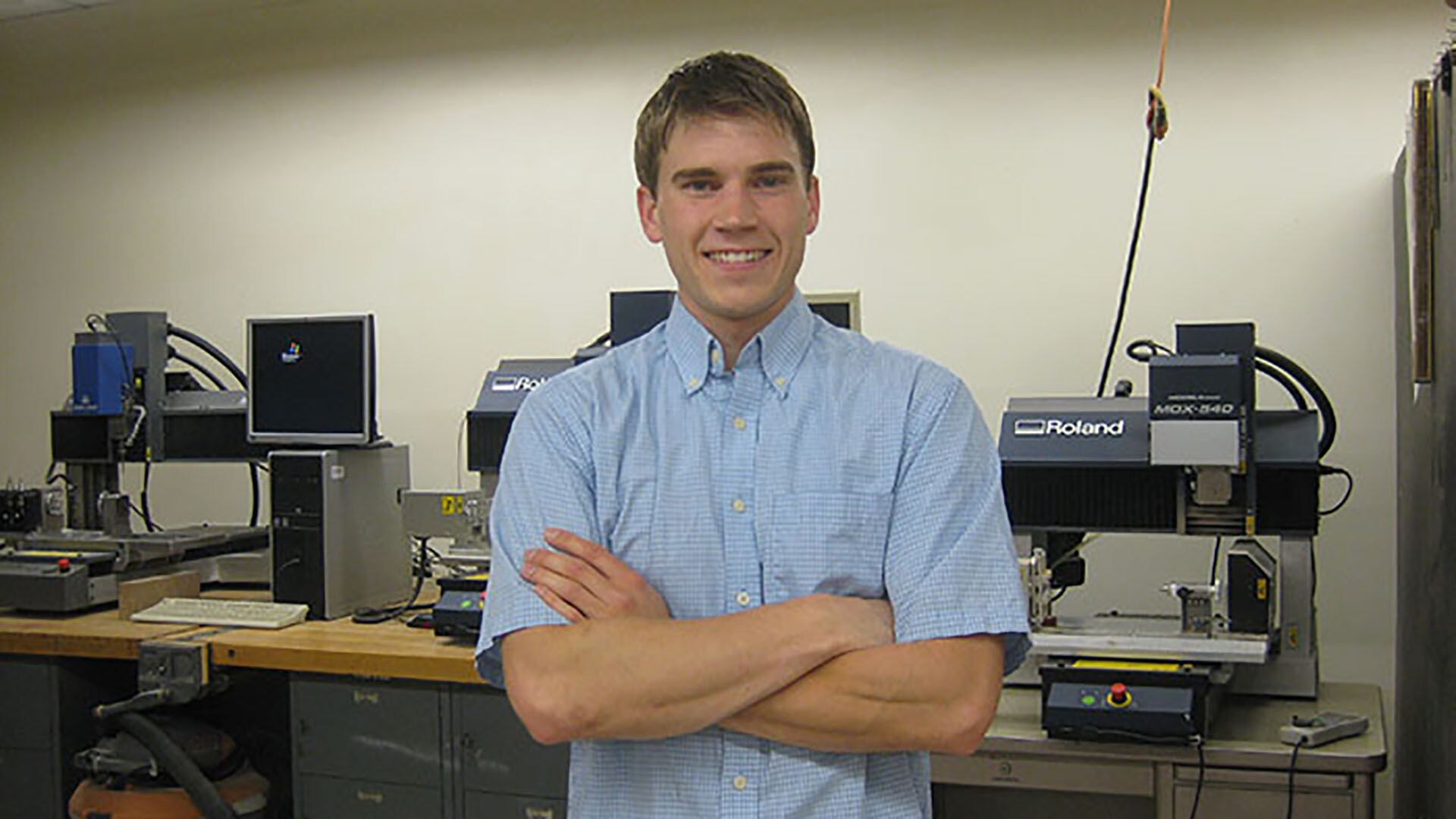Student standing in front of small table top milling machines