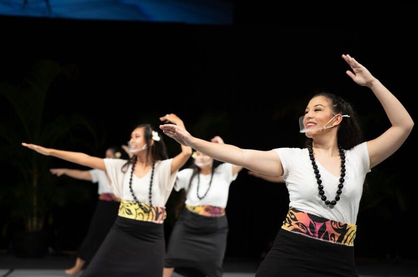 Haverly dances in front with other women behind her with their arm above their head and the other one in front of them wearing a white shirt, black kukui nut lei, and black skirt with purple/pink/orange/yellow designs on it.