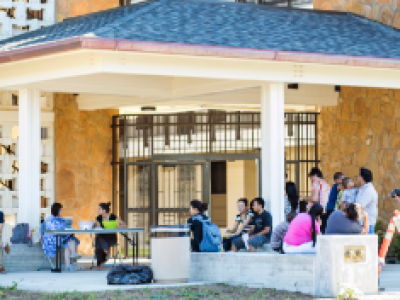 This is picture of the latest student dorm. In this image, people are gathered in the front of the dorm and relax.