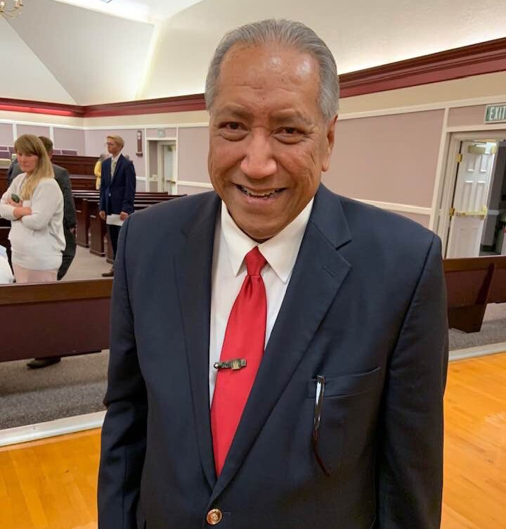 John Muaina standing in a suit and tie in a church building.