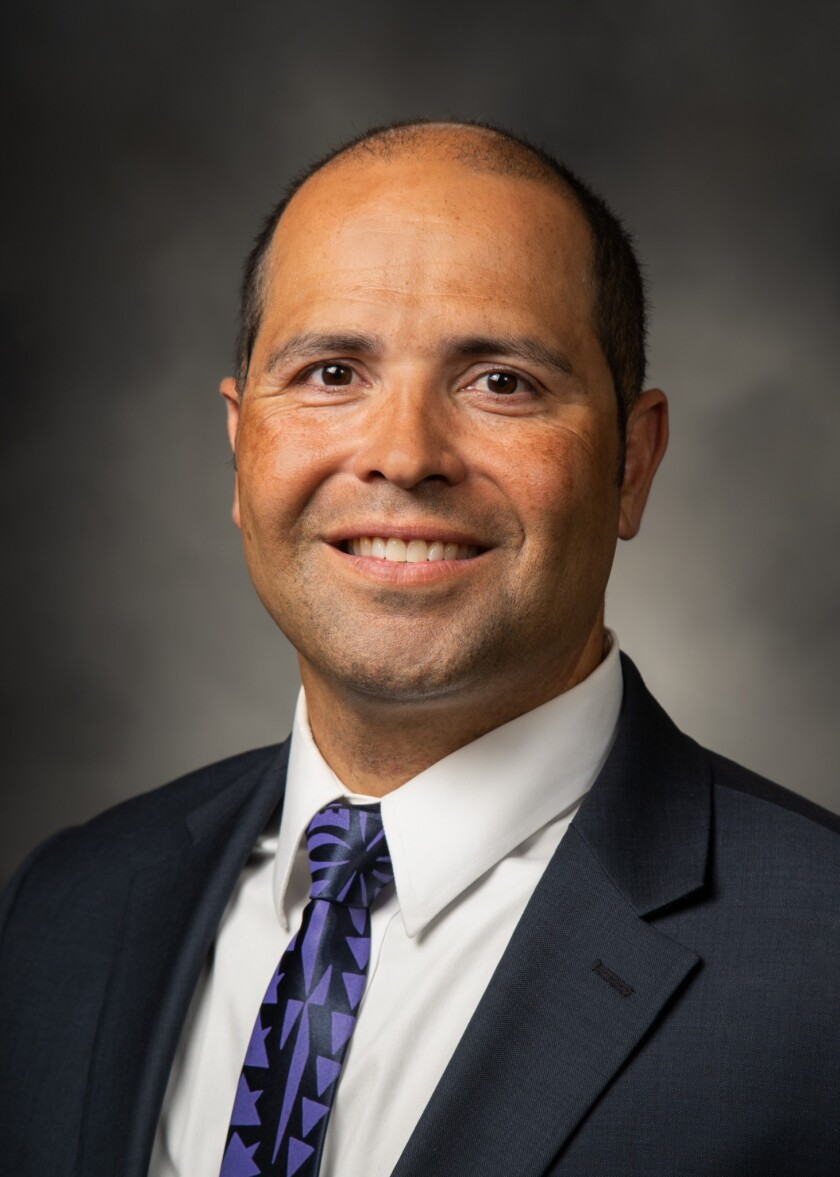 John Kauwe smiles in a suit and purple tie with patterns on it.