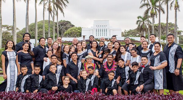 The Ah You family, comprised of more than 40 people, stand in matching white and black dress clothes with the Laie Hawaii temple in the background.