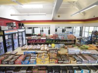 Candy, drinks, chips, bread, and other convenience store items on shelves and refrigerators