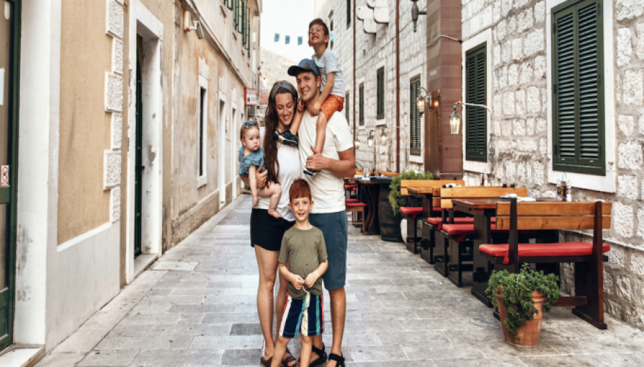 Jonathan and Alyssa Scalese stand on a stone street with their three children