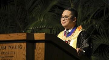 Terrence A. Dela Peña wearing graduation robes at a podium.