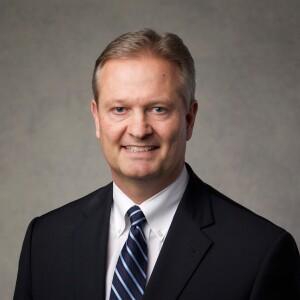 Elder Brett Nattress head portrait, wearing a black suit and striped blue tie.
