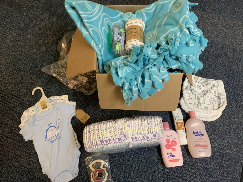 A cardboard box with baby wash and baby lotion, two light blue and white onesies, diapers, a blue blanket, socks, a white bib and a white swaddler blanket