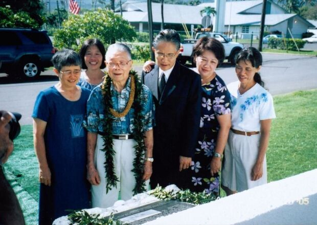 Charles K.C. Goo wearing two leis around his neck stands in the middle besides five other people with a black plaque in front of him and cars and a street behind him.
