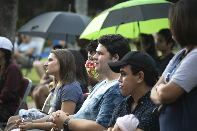 People in the audience staring in front of them, one man masked the others unmasked, with two umbrellas in the background, one black, one black and green.