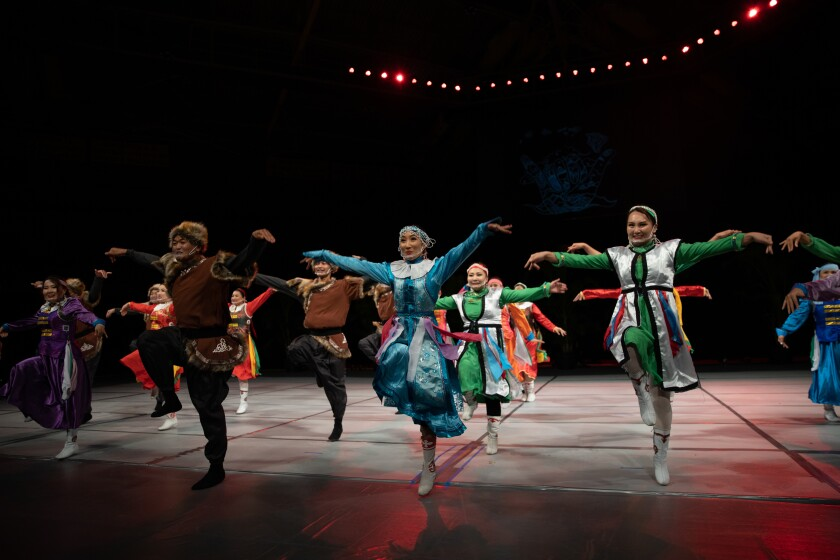 Women wearing traditional Mongolian multicolored silk dresses and men wearing clothes of brown fur and hats all with one leg up and their arms out dancing on stage.