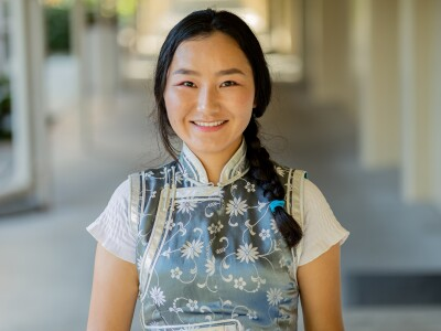 Gantulga smiles wearing a Mongolian blue and white shirt and holding a book in her hands.