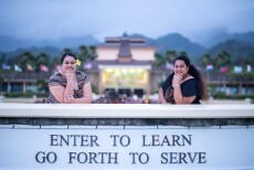 "Two women, Tanuvasa (left) and Leota (right) have their elbows resting on the sign, ""Enter to learn go forth to serve,"" in front of the BYU–Hawaii campus."