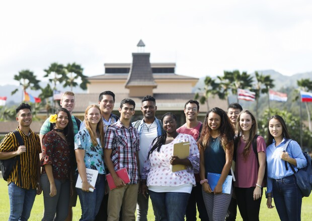 Group of students standing in front of the McKay foyer, smiling