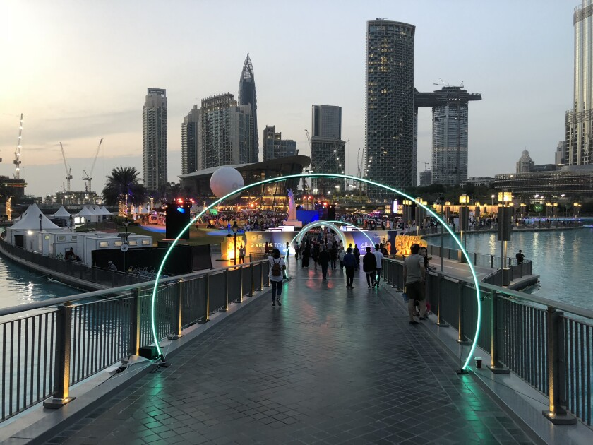 The World Expo 2020 site in Dubai with a lit pathway and skyscrapers in the background.