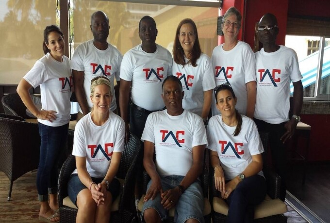 Members of The American Campus staff wear white TAC shirts and smile at the camera