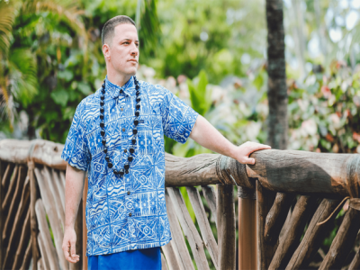 Wearing an aloha shirt and kukui nut lei, Jeremy Hawkins stands by a wooden fence at the Polynesian Cultural Center