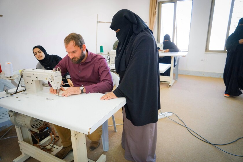 Chris Udall using a sewing machine with two women in burqas watch him. Two other women in the background in a white room.