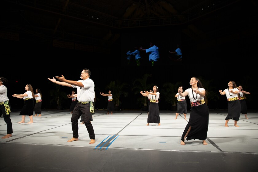 Men and women dance wearing white shirts, black skirts or pants and multicolored sashes around their waists with their arms out in front of them on a white stage.