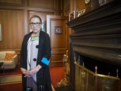 Ruth Bader Ginsburg crossing her fingers together standing in her warmly colored wooden-walled office with a fireplace on her right-hand side.