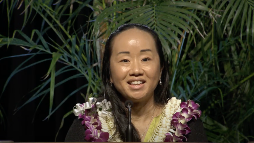 Linda Furuto speaking with a slight smile on her face with a palm tree and black background wearing two flower leis around her neck.