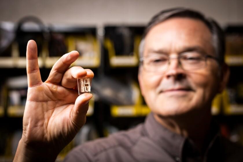 BYU professor Greg Nordin holding a tiny microfluidic device close to the camera.