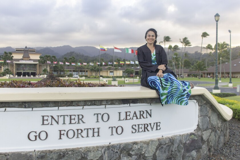 "Mataoa sits on the stone and white sign saying ""Enter to learn go forth to serve"" while wearing a patterned blue and green dress with the flags and front of BYUH campus in the background."