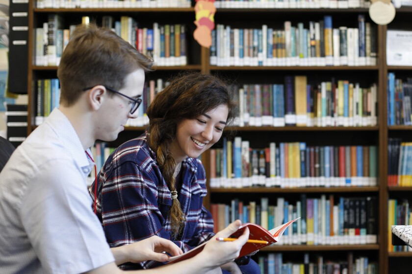 Male and female student reading a workbook in front of a shelf of books