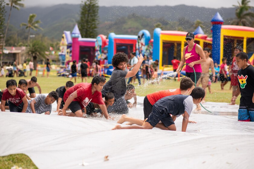 12 local children, all boys, crawling down the slip n' slide while a woman in a pink tank top uses a hose to keep the slide slippery. Four bounce houses and more children are blurry in the background.