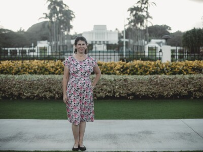 Suzanne Bowen standing in dress in front of Laie, Hawaii Temple.