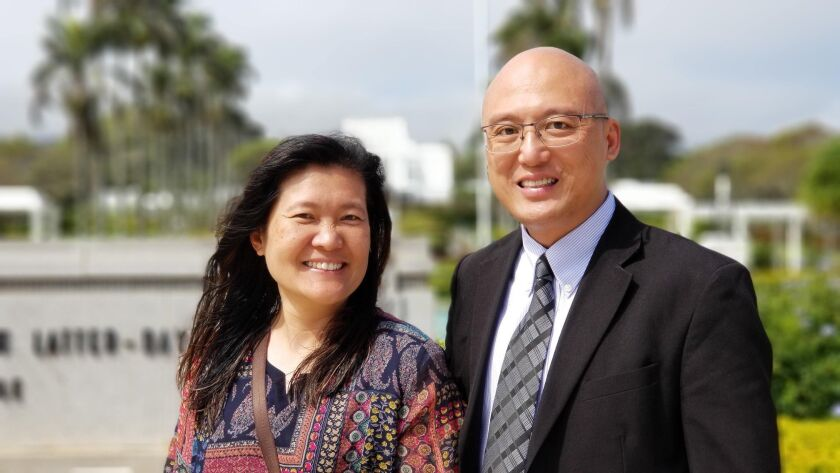 Photo of Joyce Tan and her husband standing in church clothes in front of the Laie Hawaii Temple.